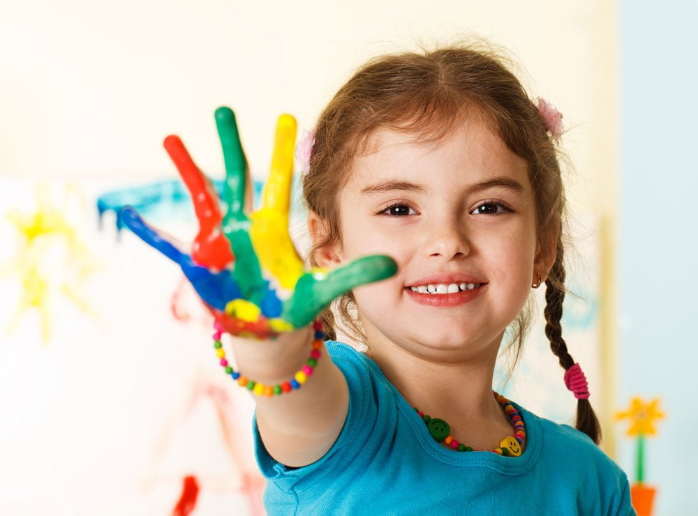 five-year-old-girl-with-hands-painted-in-colorful-paints-ready-for-hand-prints